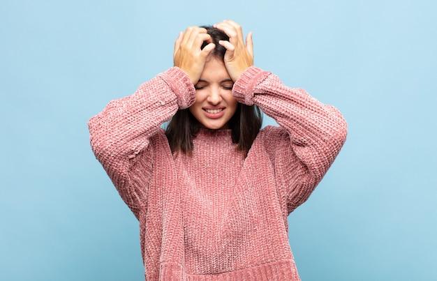 젊은 예쁜 여자는 스트레스와 불안, 우울하고 두통으로 좌절감을 느끼고 양손을 머리로 들어 올립니다.
