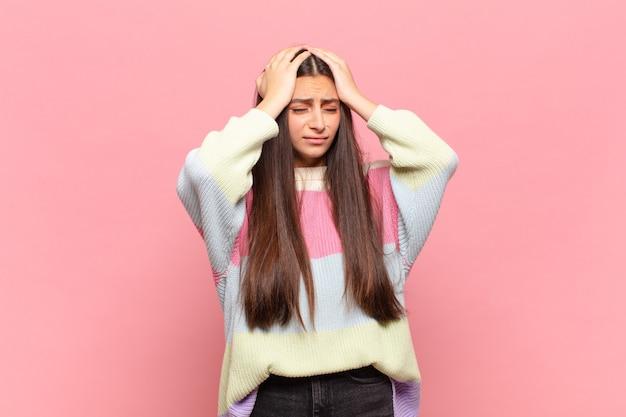 ストレスと不安を感じ、頭痛で落ち込んで欲求不満を感じ、両手を頭に上げている若いきれいな女性