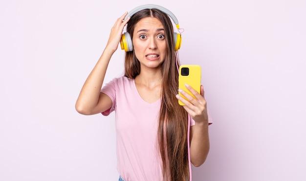 若いきれいな女性は、頭に手を置いて、ストレス、不安、または恐怖を感じています。ヘッドホンとスマートフォン