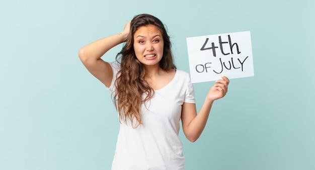 Молодая красивая женщина чувствует себя подчеркнутой, взволнованной или напуганной, с руками на голове концепция дня независимости