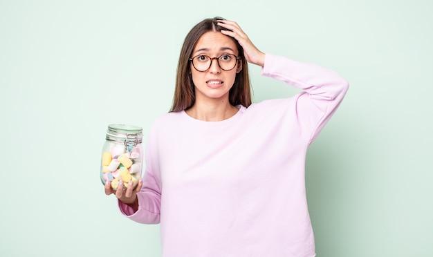 頭に手を置いて、ストレス、不安、または恐怖を感じている若いきれいな女性。ゼリーキャンディーのコンセプト
