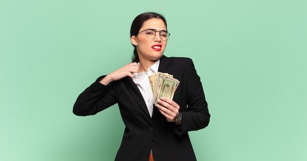 젊은 예쁜 여자는 스트레스, 불안, 피곤하고 좌절감을 느끼고 셔츠 목을 당기고 문제로 좌절감을 느낍니다. 비즈니스와 지폐 개념