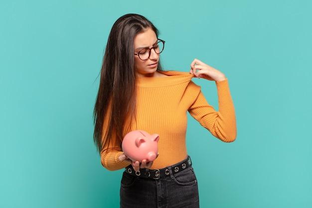 젊고 예쁜 여성은 스트레스, 불안, 피곤, 좌절감을 느끼며 셔츠 목을 당기고 문제에 대해 좌절감을 느끼고 있습니다. 돼지 저금통 개념