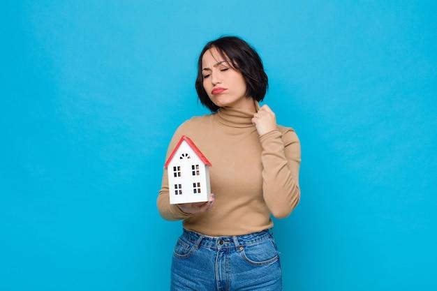 若いきれいな女性のストレス、不安、疲れ、欲求不満、シャツの首を引っ張って、家のモデルの問題に不満を感じて