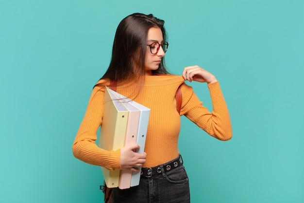 ストレス、不安、疲れ、欲求不満を感じ、シャツの首を引っ張って、問題で欲求不満に見える若いきれいな女性