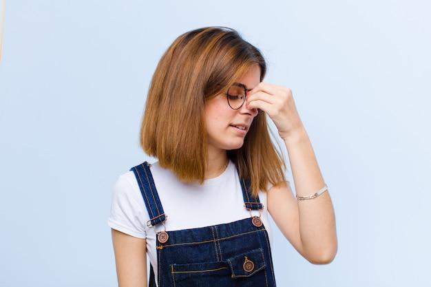 若いきれいな女性のストレス、不幸、イライラ、額に触れる、青い背景に激しい頭痛の片頭痛に苦しんで