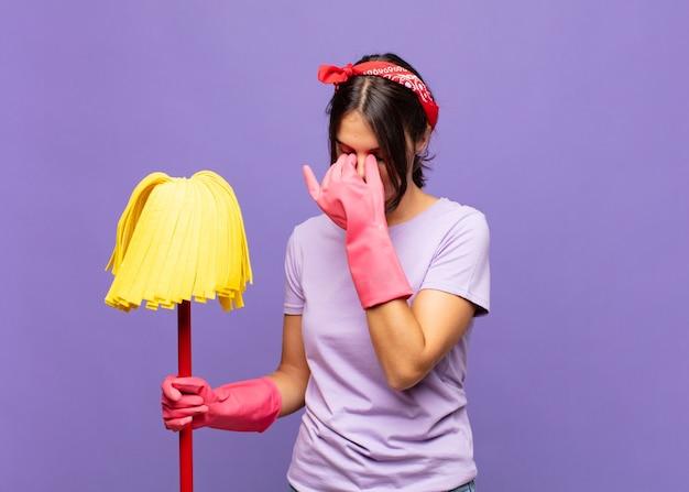 Молодая красивая женщина чувствует себя подчеркнутой, несчастной и разочарованной, касается лба и страдает от сильной мигрени