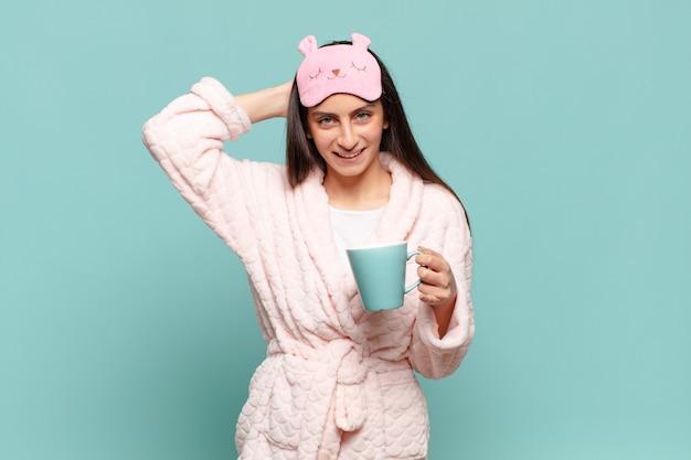 若いきれいな女性は、頭に手を置いて、ストレス、心配、不安、または恐怖を感じ、誤ってパニックに陥ります。パジャマのコンセプトを身に着けて目を覚ます