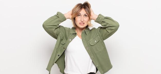 若いきれいな女性は、頭に手を置いて、ストレス、心配、不安、または恐怖を感じ、誤ってパニックに陥る