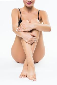 Gambe femminili della giovane donna graziosa isolate sulla parete bianca