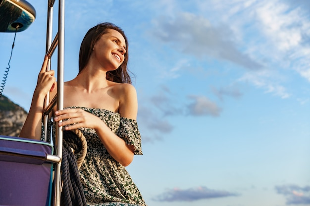 Young pretty woman in floral dress posing on yacht in the sea