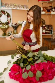 花束を持って若いきれいな女性の花屋