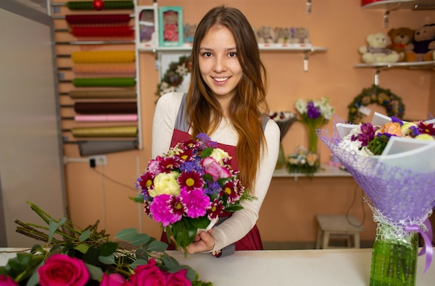 Young pretty woman florist holding a bouquet while standing at the stall of a flower shop