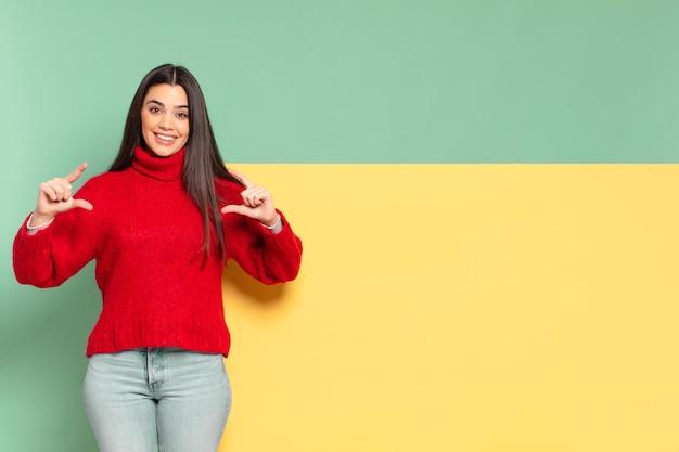 젊고 예쁜 여성이 양손으로 자신의 미소를 짓거나 윤곽을 그리며 긍정적이고 행복해 보이는 웰빙 개념입니다. 개념을 배치할 공간 복사