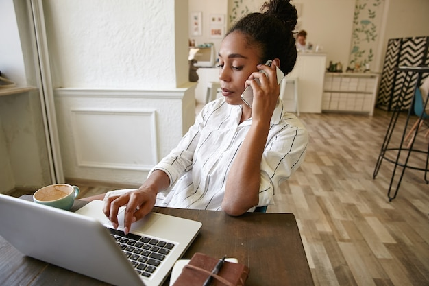 喫茶店からリモートで作業し、スマートフォンで電話をかけ、ラップトップのキーボードでメッセージを入力する若いきれいな女性のフリーランサー