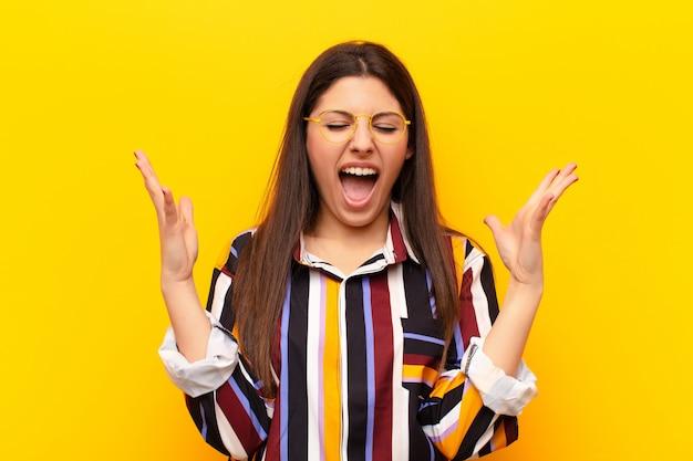 Молодая симпатичная женщина яростно кричит, чувствуя стресс и раздражение с поднятыми вверх руками, говоря, почему я против желтой стены
