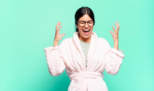 Молодая симпатичная женщина яростно кричит, чувствуя стресс и раздражение, подняв руки вверх, говоря, почему я. концепция пижамы