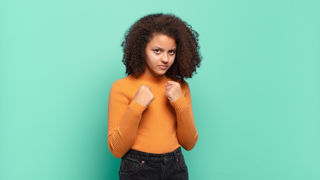 Young pretty woman gesturing on colored wall