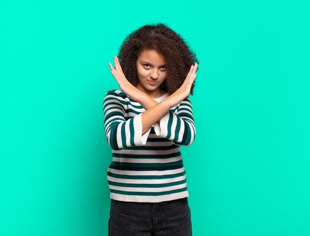 Молодая красивая женщина, жестикулирующая на цветной стене