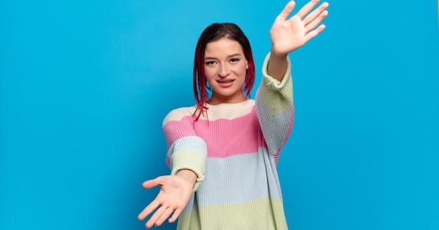 色付きの壁に身振りで示す若いきれいな女