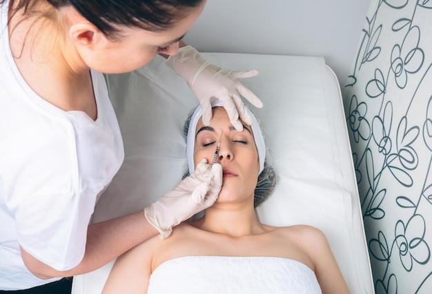 클리닉 치료의 일부처럼 얼굴에 화장품 주사를 맞는 젊은 예쁜 여자. 의학, 건강 관리 및 미용 개념입니다.