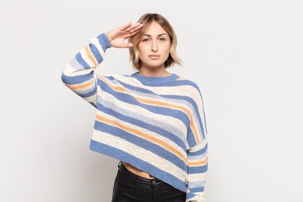 Молодая красивая женщина приветствует камеру военным салютом в знак чести и патриотизма
