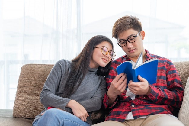 Young pretty woman and handsome man reading on sofa