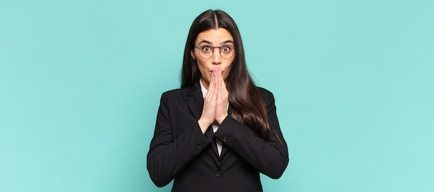 Молодая симпатичная женщина счастлива и взволнована, удивлена и поражена, прикрывая рот руками, хихикая с милым выражением лица. бизнес-концепция