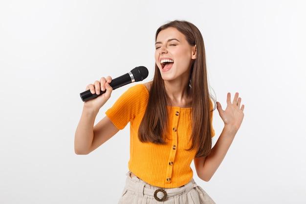 Молодая симпатичная женщина счастлива и мотивирована, поет песню с микрофоном, представляет событие или устраивает вечеринку, наслаждается моментом