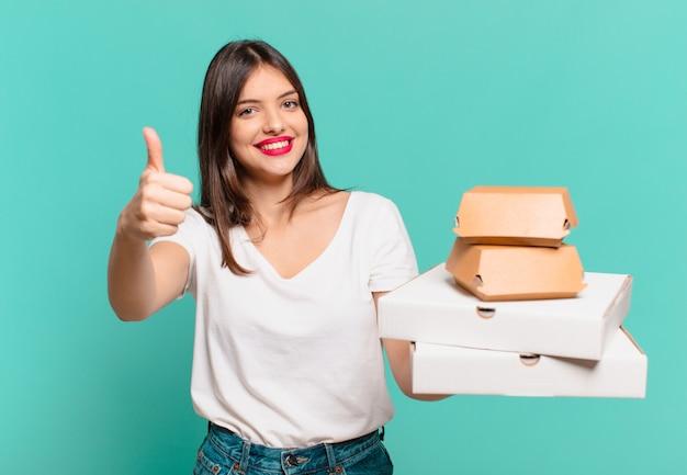 Молодая красивая женщина счастливым выражением и держит пиццу на вынос