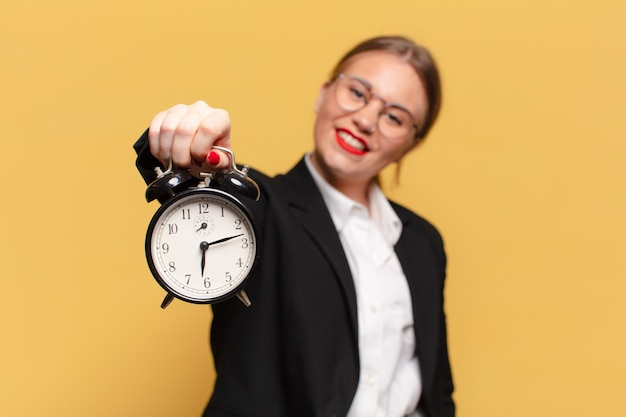 Young pretty woman. happy and surprised expression. alarm clock concept