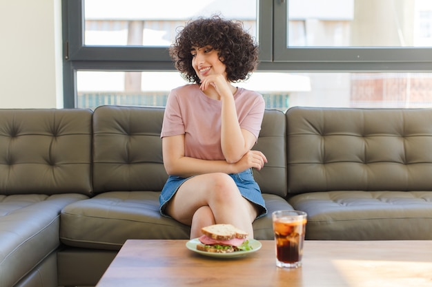 Young pretty woman having a sandwich sitting on a sofa at home