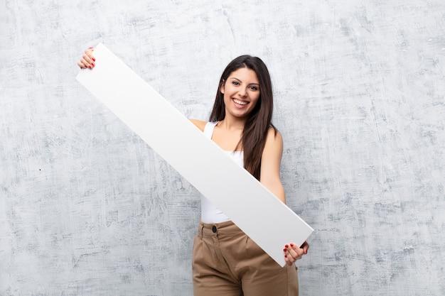グランジ壁にバナーを保持している若いきれいな女性
