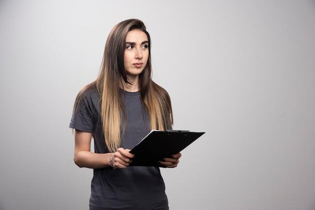Молодая красивая женщина, держащая буфер обмена на сером фоне.