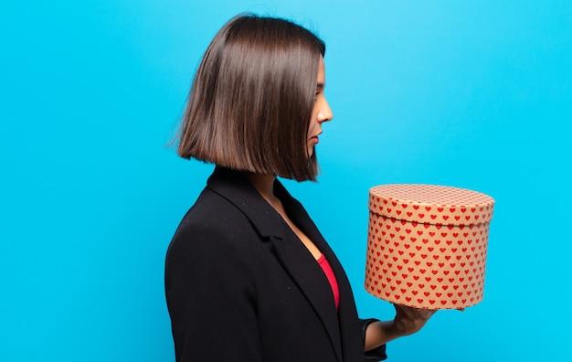Молодая красивая женщина держит подарочную коробку