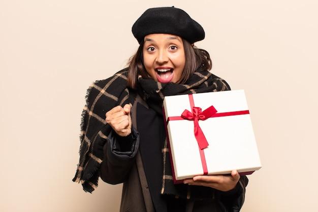 贈り物を持っている若いきれいな女性