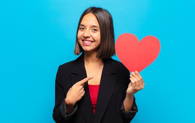 Молодая красивая женщина, держащая сердечную карту