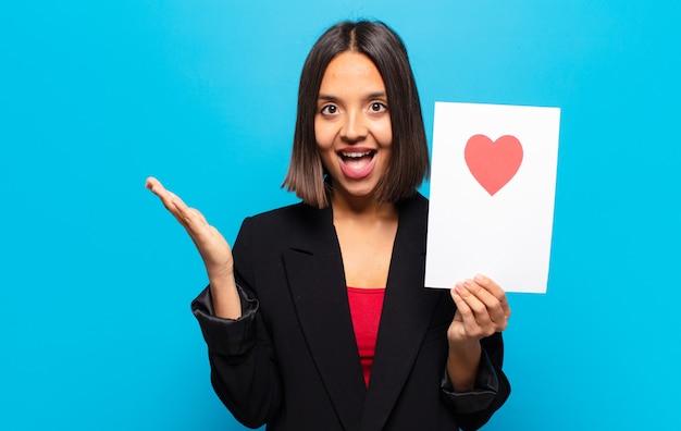 ハートカードを持っている若いきれいな女性