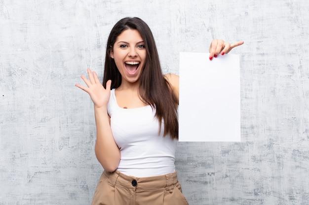 グランジセメント壁に紙のシートを保持している若いきれいな女性