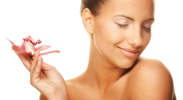 Молодая красивая женщина держит розовую орхидею с закрытыми глазами, изолированную на белом пространстве, крупным планом