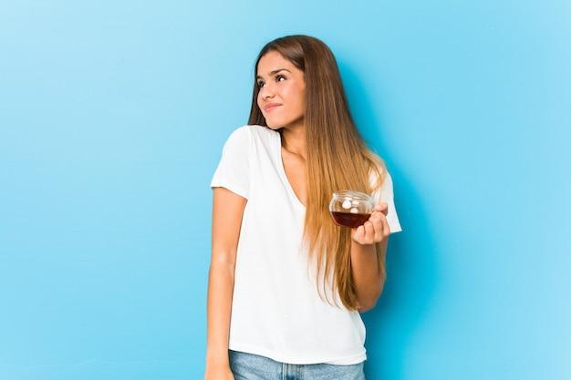 Молодая красивая женщина, держащая чашку чая, мечтающая о достижении целей и задач