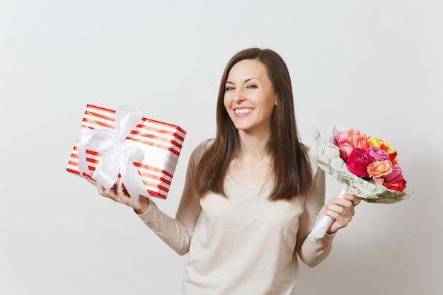 아름 다운 장미 꽃의 꽃다발을 들고 젊은 예쁜 여자, 선물 상자 흰색 배경에 고립. 광고 공간을 복사합니다. 성 발렌타인 데이 또는 국제 여성의 날 개념