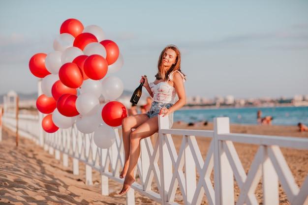 シャンパンと風船と海に対してビーチでフェンスに座っているガラスを保持している若いきれいな女性