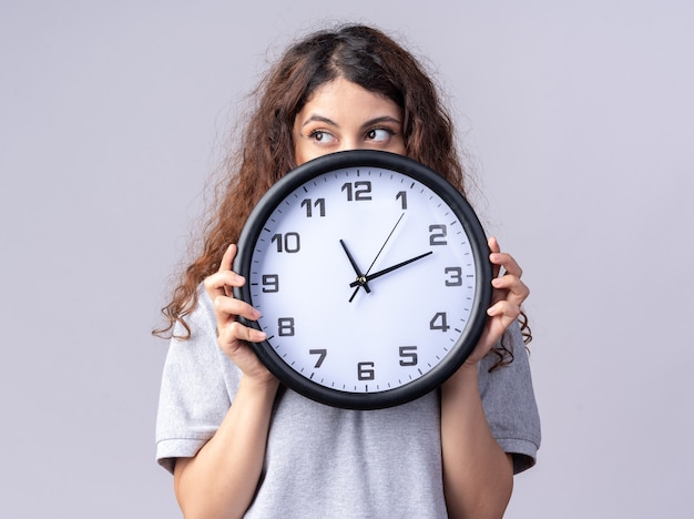 Giovane bella donna che tiene l'orologio guardando il lato da dietro isolato sul muro bianco
