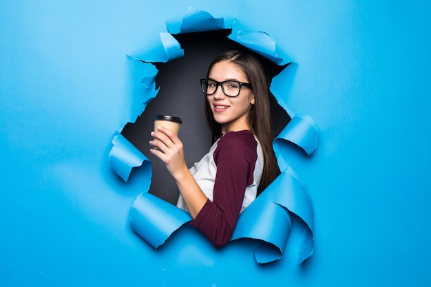 Young pretty woman holding coffee while looking through blue hole in paper wall.