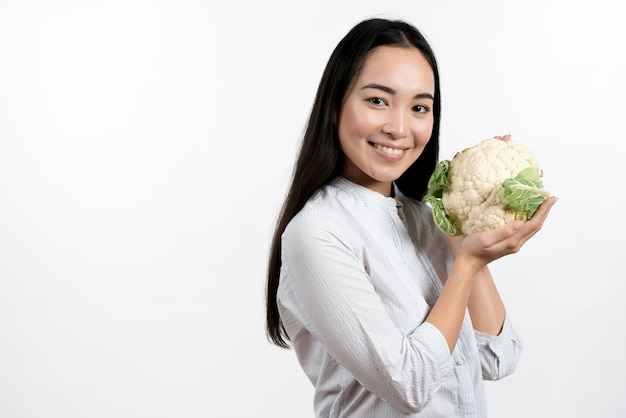 Young pretty woman holding fresh cauliflower in front of white background