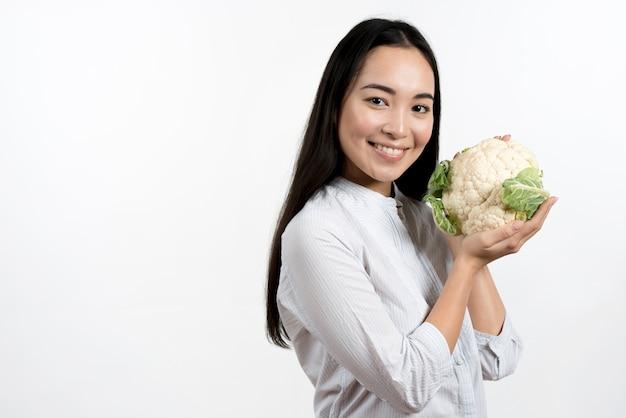 Молодая милая женщина держа свежую цветную капусту перед белой предпосылкой