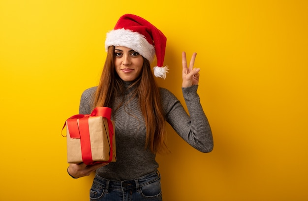 Young pretty woman holding gift fun and happy doing a gesture of victory