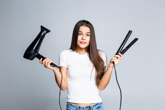 Молодая милая женщина держа фен для волос и выправлять изолированный на белизне