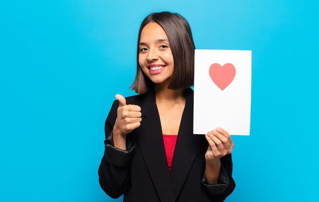 Young pretty woman holding a heart card
